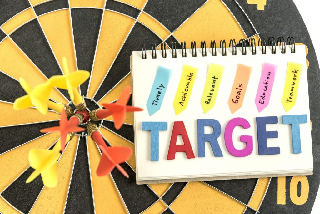 six dart in bullseye with words target on the notebook with hand