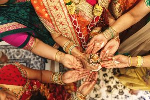 All the Indian family women hold spices on their palms