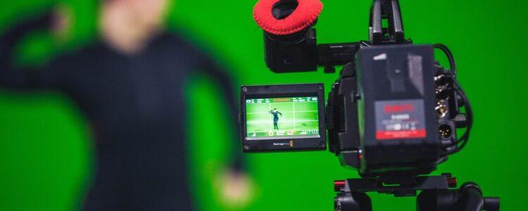 Bagi kamu yang berkecimpung di dunia perfilman atau sedang sekolah film, pasti udah nggak asing dengan penggunaan green screen. Apalagi untuk beberapa genre film yang membutuhkan efek visual khusus, seperti film science fiction, superhero, atau film-film fantasi penggunaan green screen adalah hal yang penting. Para kreator film menggunakan green screen sebagai alat bantu untuk memudahkan proses syuting dan memberi efek visual yang super keren. Apa Itu Green Screen? Green screen merupakan sebuah media yang digunakan sebagai backdrop saat proses syuting, sehingga background asli bisa dimanipulasi menjadi background digital dengan memberi efek visual sesuai konsep yang diinginkan. Nantinya dengan sentuhan tangan ajaib para video editor, kamu bisa dengan mudah membangun setting dan properti tempat yang tidak mungkin ada di bumi. Selain itu, kamu tidak perlu membangun set mewah atau menyewa studio yang tentunya akan menguras banyak biaya. Kamu bisa merekam video di mana saja, lalu ganti background dengan elemen grafis, foto-foto, maupun video. Kunci Utama Green Screen adalah Pencahayaan Pengaplikasian teknik green screen saat sesi produksi sangatlah mudah. Kamu cukup menggunakan kain hijau untuk menutupi semua background video yang masuk di layar kamera. Jika sudah selesai syuting, kamu tinggal mengedit background sesuai dengan yang diinginkan menggunakan software editing, seperti Adobe After Effects. Di dalam Adobe After Effects sudah ada fitur efek, yaitu chroma key yang bisa langsung mendeteksi warna hijau dan mengubahnya menjadi transparan. Namun perlu diingat, jika ingin menghasilkan video yang terlihat nyata, salah satu triknya adalah dengan mengatur pencahayaan yang tepat. Misalnya pada saat syuting pencahayaan gambar cenderung gelap, tapi background video yang nantinya akan kamu pakai untuk mengganti green screen cenderung terang. Alhasil bila keduanya digabungkan, maka akan sangat terlihat palsu. Kenapa Green Screen Warnanya Hijau? Pada umumnya green screen yang